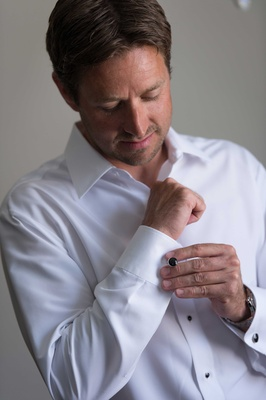 Groom getting ready for wedding day in white button up down shirt with black cufflinks