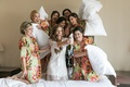 bridesmaids in green floral robes prepare to hit the bride with pillows as she pops Champagne
