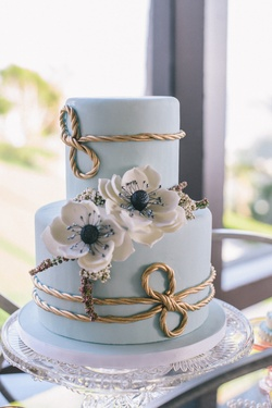 Light blue wedding cake with gold rope details and white sugar anemones