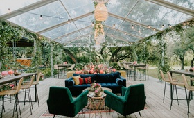 wedding reception clear tent rattan pendant chandelier velvet lounge furniture bar stools lights