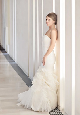 chicago bride poses against a white wall in a fitted mermaid wedding dress by vera wang