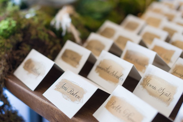 tent escort cards on wood table black calligraphy gold brush stroke paint detail