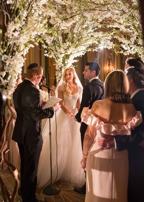 couple getting married by jewish rabbi under a chuppah made of foliage and white flowers
