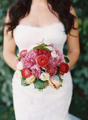 Bride in gown holding pink and red flowers