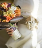 Bride holding purple, green, and orange autumn flowers