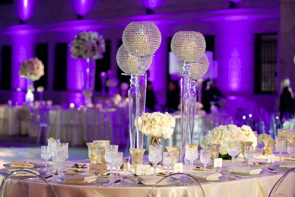 Purple lighting at wedding reception with ivory wedding flowers and crystal candle votives