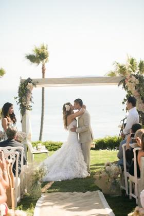 Katrina Hodgson and Brian Scott kiss under wedding arch