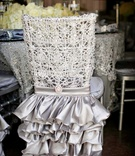 Silver ruffle chair skirt at opulent wedding reception with lacelike cover