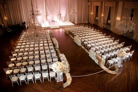 Wood floor ballroom white drapery white ceremony chairs flower petals and walls along aisle ribbon