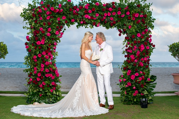 bride in strapless wedding dress with groom in white suit pink shirt under greenery arch pink roses