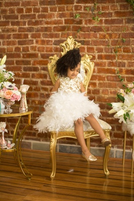 pantora mini flower girl dress with white feathers for skirt and gold detail on bodice