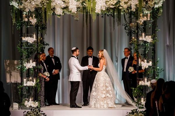 wedding ceremony chuppah four post candles greenery white flowers contrasting palette natural decor