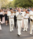 wedding guests walking streets with mariachi band inspired by san miguel de allende callejoneada