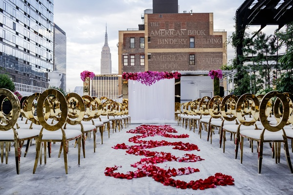 Gold chairs white cushions flower petal swirl aisle runner white drape altar brick skyline empire