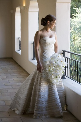 Bride in a strapless Vera Wang gown with champagne bands holds bouquet of orchids