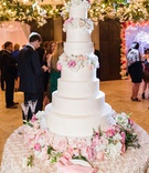 white wedding cake with seven tiers with fresh flowers