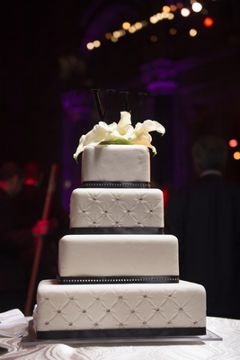 White wedding cake with quilted layers dotted with rhinestones, topped with white calla lilies