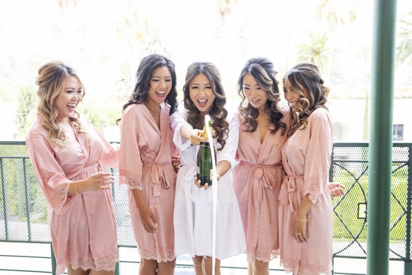 bride in white robe and four bridesmaids in pink robes champagne bubbles pop on balcony
