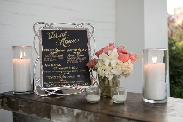 black drink menu with gold writing and silver looped frame