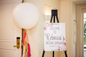 wedding ideas bridal shower sign on easel large white balloon with gold pink red orange tassels