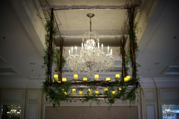 Crystal chandelier surrounded by branch and greenery
