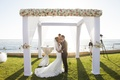Bride in wedding dress and groom in tuxedo kiss at oceanfront wedding ceremony in Mexico