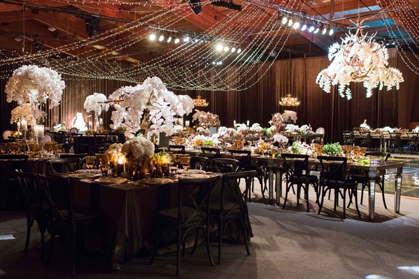 Barn wedding reception Aspen ranch with dark colors, white flowers, antlers, string lights