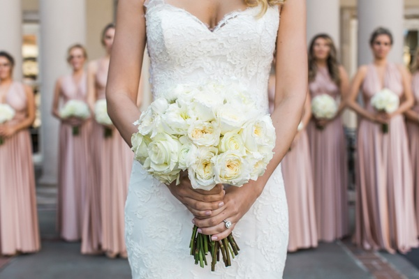 Bride holds bouquet with bridesmaids behind her