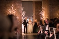 Brick wall led trees winter wedding bride entering ceremony space with father and mother black dress