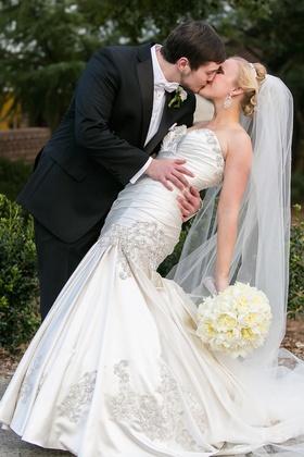 Man in tuxedo kissing woman in wedding dress