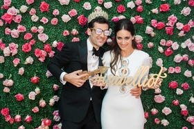 Groom in hashtag sunglasses with crown and bride in after-party dress with hashtag sign photo booth