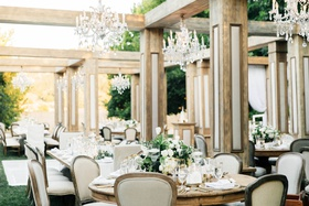 Jillian Murray and Dean Geyer wedding wood structure over tables chandeliers classic glam decor