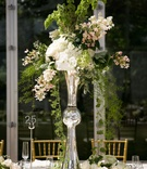 Trumpet vase centerpiece with green vines and white flowers