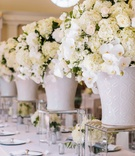 White wedding reception decor, white hydrangea, orchid, rose centerpiece in ginger jar on lucite