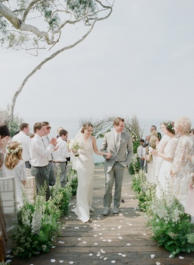 Outdoor wedding on wood planks with green and white flowers