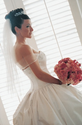 Bride in ball gown holds bouquet in bridal suite