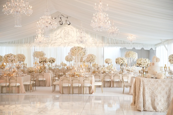 Neutral tent wedding reception white tall flower centerpieces linens dance floor chandeliers