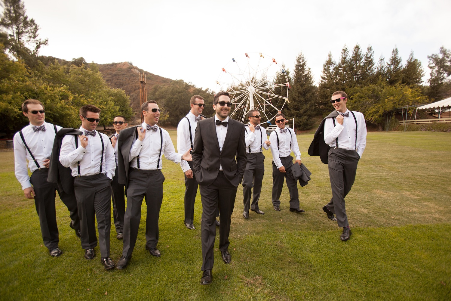 Groomsmen walk in front of ferris wheel