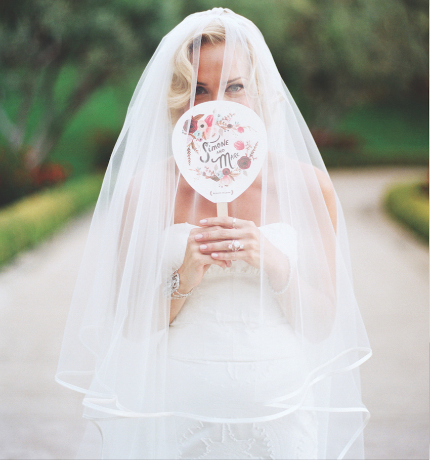 Bride with veil holding flower print program fan