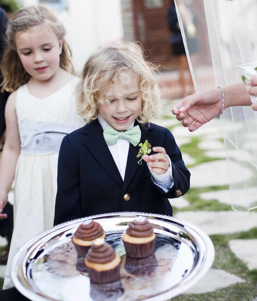 Blond boy looking at chocolate cupcakes