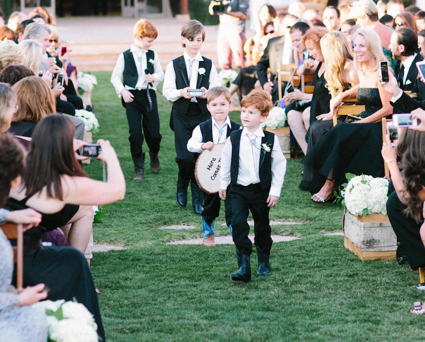 Ring bearers in bolo ties carrying wood sign