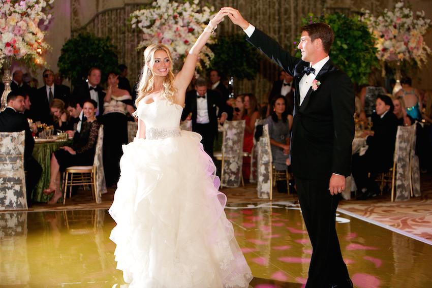 Groom spins bride in ball gown on dance floor