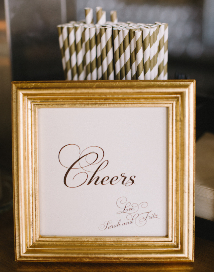 Cheers print in gold frame at wedding bar