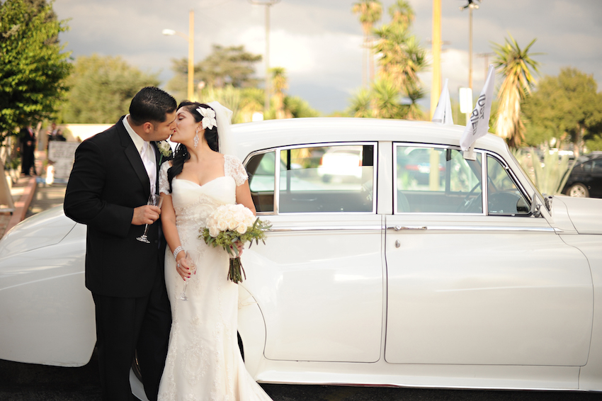 Bride and groom in front of white wedding car