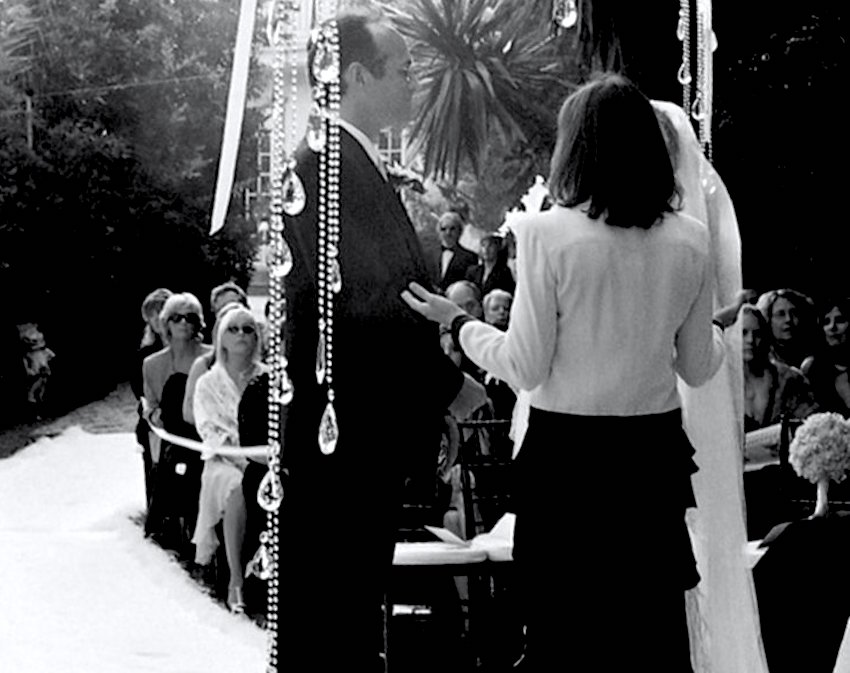 Black and white photo of two empty chairs at ceremony