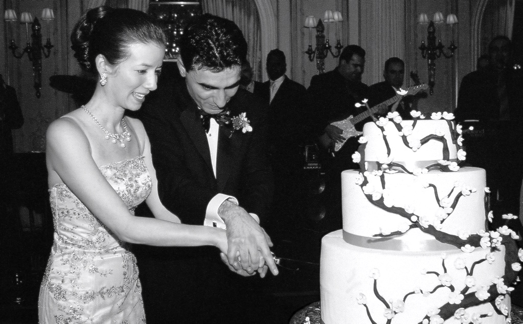Black and white photo of bride and groom cutting cake