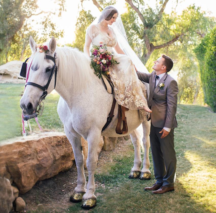 Bride in Claire Pettibone on white horse at wedding