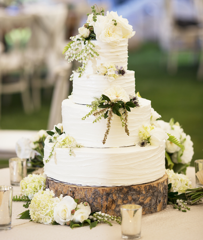 White wedding cake on rustic wood slab