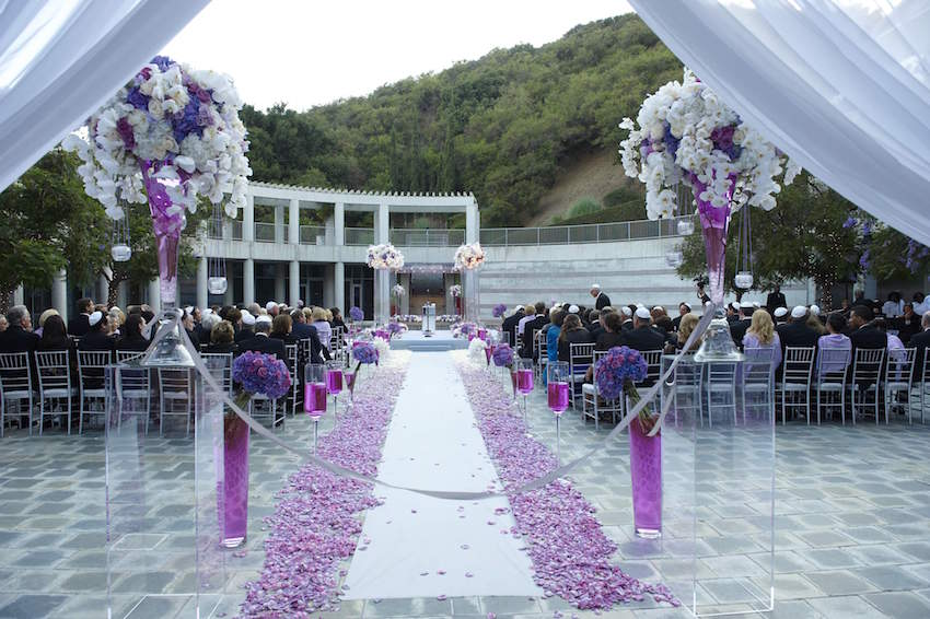Purple flowers along outdoor ceremony aisle