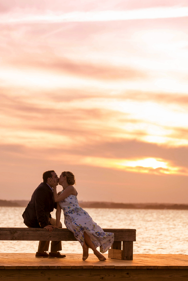 Kissing engagement shoot picture on pier at sunset